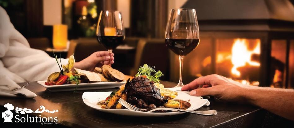 2 personas cenando y tomando vino en copa de vidrio